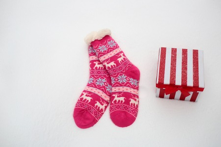 Pair of socks and gift box on snowy background. Knitted socks with ornament and present pack on white snow. Christmas and new year surprise. Winter holidays celebration concept