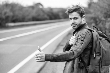 Young guy with beard on sexy serious handsome face in casual clothes black backpack standing near road way hitchhiking autostop with hand outdoor Stock Photo