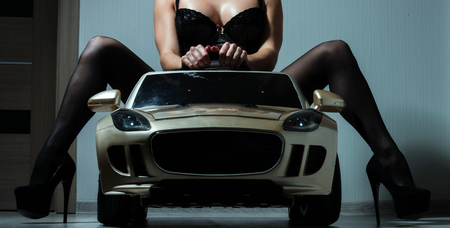 Woman in black lingerie and shoes. Girl in car toy. Driver girl sit in car. escort and sexual services. Beauty and fashion.