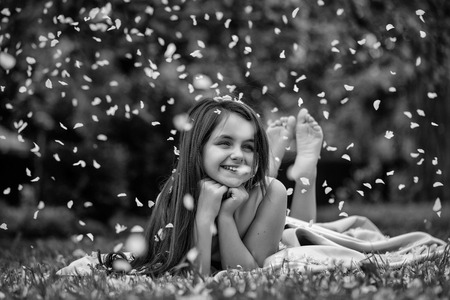 Beautiful little girl in pink dress with long brunette hair and smiling face lying barefoot on green grass in spring flower blossom petals outdoor