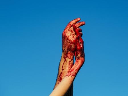 ゾンビの手の男性と男の戦争の兵士と女の子、または青い空の背景の皮膚に赤い血を持つ女性の女性