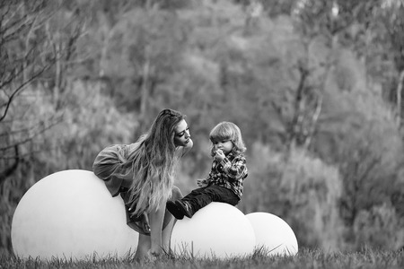 Young beautiful woman and small boy with big ball in park outdppr