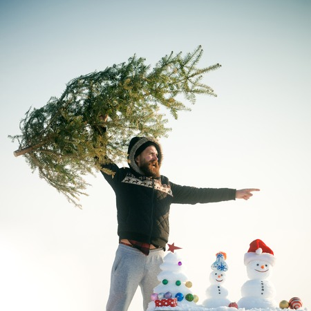 Hipster raising xmas tree and pointing finger. Snowman and snowy sculptures on white sky. Christmas and new year. Winter holiday celebration concept.