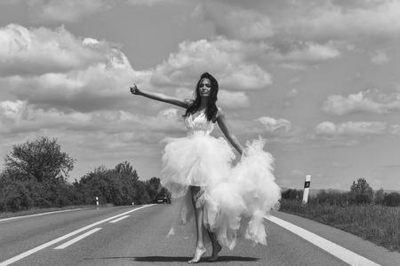 junge Hochzeit glücklich sexy Mädchen oder eine Frau mit brünetten Haaren und hübsches Gesicht in weißen Braut Kleid Stop-Auto auf der Straße Weg mit Daumen bis auf bewölkten blauen Himmel Hintergrund mit grüner Natur