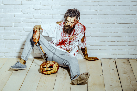 Halloween bearded hipster with red blood splatters. Psychopath bleeding in torn tshirt. Maniac and bloody jack o lantern. Halloween holiday concept. Man sitting with pumpkin and axe on wooden floor.