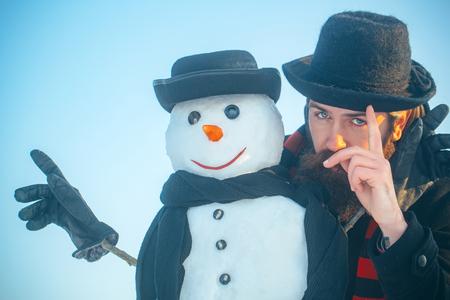Sneeuwman en man in herenpetten en sjaals. Hipster met opgeheven wijsvinger. Sneeuwbeeldhouwwerk met handschoenen op blauwe hemel. Kerstmis en Nieuwjaar concept. Wintervakanties Stockfoto - 86755449