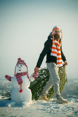 Hipster slepende Kerstmis boom op besneeuwde winter weg. Mens en sneeuwman die op blauwe hemel lopen. Kerstmis en Nieuwjaar. Kerel en sneeuwbeeld die hoeden en sjaals dragen. Vakantie feest concept.