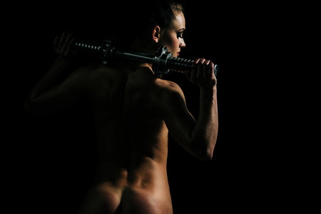 Activity and energy. Woman with naked body at workout. Sexy girl with metallic dumbbell or barbell. Coach and health. Sport and weightlifting. Stock Photo