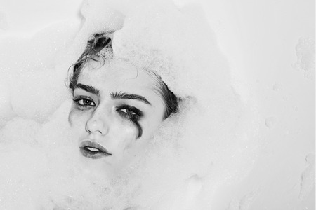 Closeup view portrait of one beautiful sensual sexy attractive young woman with wet bright makeup lying in bath tub with water and lots of white soap foam looking away copy space, horizontal picture