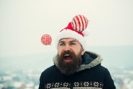 クリスマスと新年のお祝い。雪景色のクリスマス ボールをジャグリング サンタ男。冬の休日のコンセプトです。幸せなヒップスター喜びで口を開き