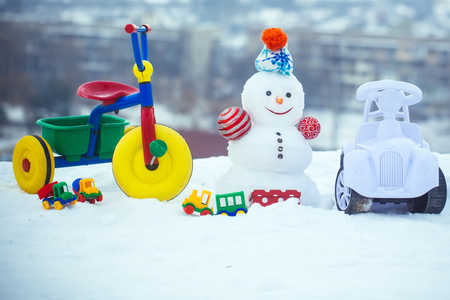 Snowman with smiley face on winter landscape. Tricycle, car and toys on snowy background. Christmas and new year. Festive surprise and presents. Holidays celebration concept.