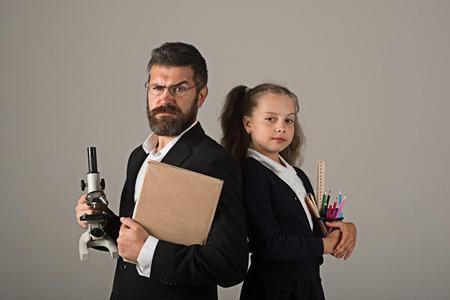 スーツと制服の女の子と男。灰色の背景にトリッキーな笑顔の顔を持つ父と女子高生。家庭教育と学校のコンセプトに戻る。子供とパパは、顕微鏡