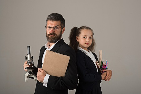 Girl and man in suit and school uniform. Father and schoolgirl with tricky smiling faces on grey background. Home schooling and back to school concept. Kid and dad hold microscope, book and stationery