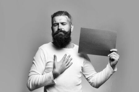 young bearded man with serious face holding red paper sheet in studio on grey background, copy space Stok Fotoğraf