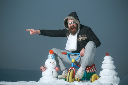 Excited man riding tricycle on grey sky. Holiday celebration concept. Hipster in pilot glasses and hood pointing finger. Christmas and new year fun. Snowman and snow xmas tree on winter landscape.