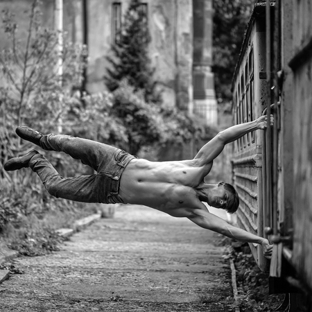Handsome young guy with muscular body training shirtless with beautiful torso near blue old train railcar Stock fotó