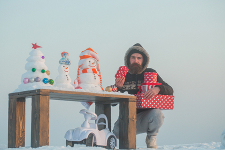 Unhappy man holding gift boxes. Hipster with presents on grey sky. Toy car under table with snowmen and xmas tree. Christmas and new year celebration. Winter holidays concept.