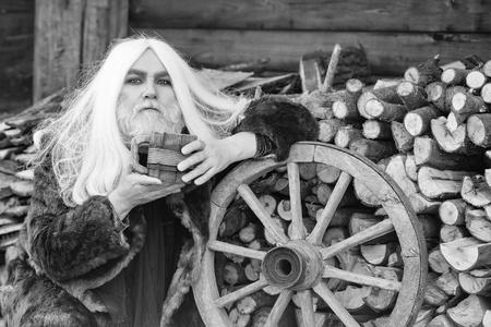 長い灰色の髪と毛皮のコートでひげを生やしたドルイドの古いひげの男は、屋外のホイールの近くに手に木製のマグカップを持っています 写真素材