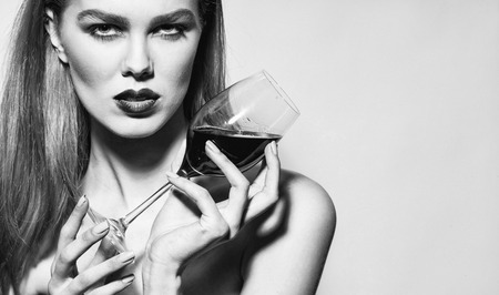 Pretty girl or sexy woman with red lips, stylish makeup, on beautiful face and long hair drinking wine, burgundy color, from glass, wineglass, on grey background, copy space 版權商用圖片