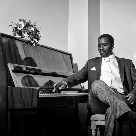 흰색 넥타이와 손수건 우아한 정장에 잘 생긴 남자 아프리카 계 미국인 신랑 결혼식을위한 주머니 광장 피아노 연주 스톡 콘텐츠