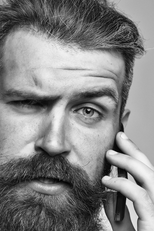 handsome young man with long dark haired beard and serious face speaking on mobile phone closeup Stock Photo