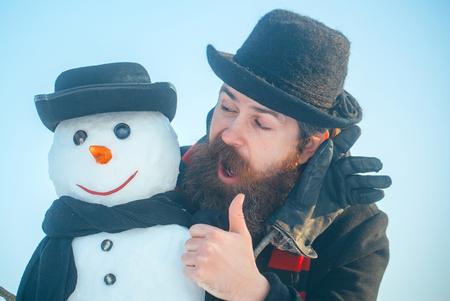 Sneeuwman met smileygezicht in handschoenen. Hipstermens met baard die duimen op hand geeft. Heren in zwarte hoeden en sjaals op blauwe hemel. Kerstmis en Nieuwjaar concept. Wintervakanties