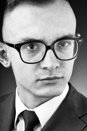 young fashion businessman with nerd glasses and stylish hairdo in jacket with tie on studio background closeup