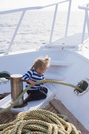 Yachting and sailing concept. Baby care and childhood. Little child sitting and berthing rope on white boat. Travel and summer vacations. Boy kid playing with rope on yacht.