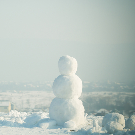 christmas snowman made of white snow in winter sunny outdoor