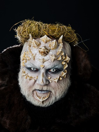 Man with hay wreath on head. Monster with dragon skin and bearded face. Demon in fur coat on black background. Alien or reptilian makeup with sharp thorns and warts. Autumn and harvest concept.