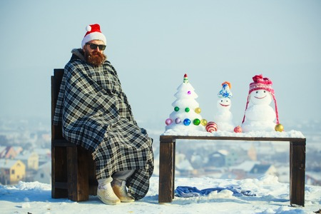 Hipster in plaid blanket sitting on chair on winter day. Man in red santa hat and glasses. Snowmen and snow xmas tree on wooden table. Christmas and new year. Holidays celebration concept