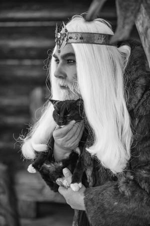 長い灰色の髪を持つドルイド老人と毛皮のコートでクラウンとひげ、暗い背景の木の猫を保持しています。