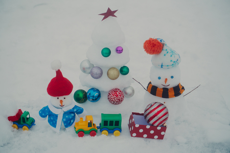Snowmen with smiley faces in clothing. Snow sculptures on rosy background. xmas and new year. Christmas tree with balls, present box, toy train and car. Winter holidays concept. 版權商用圖片