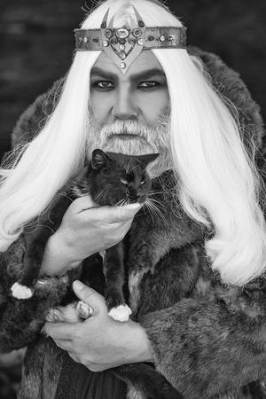 灰色の長い髪とドルイド老人と毛皮のコートでクラウンとひげは暗い背景に猫を保持します。