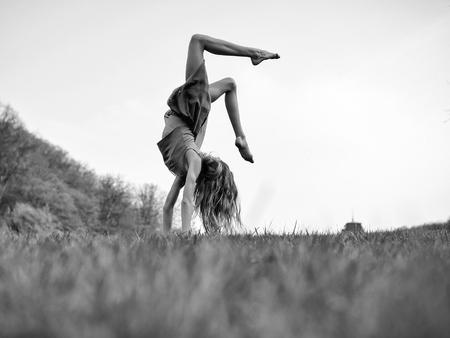 草の上で宙返りをする若い女性。スポーツとレジャー、自由