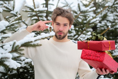 Man pointing finger with red boxes in snow wood. Macho with presents on winter day. Merry Christmas and happy new year. Season greetings and xmas gifts. Holidays celebration concept. Stock Photo