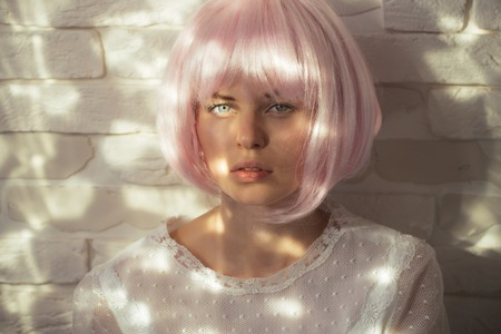 Model with cute face on white brick wall. Woman with light beams on skin. Beauty and cosmetics. Health and skincare concept. Girl posing in pink wig. Stok Fotoğraf