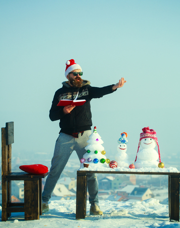 Learning and fun concept. Man santa pointing finger on winter day. Christmas and new year holidays celebration. Snowmen and snow xmas tree on wooden table. Hipster in glasses with book on blue sky.