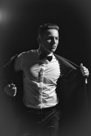 young handsome gentleman undressing fashion black suit in white shirt and bow tie in studio