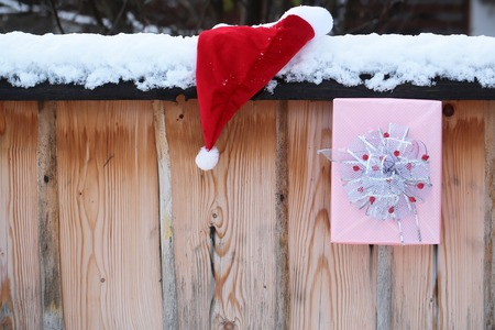 Santa presents on snowy fence. Santa claus hat and Christmas box on wooden background. New year and xmas. Winter palisade with white snow. Holidays celebration concept. Stock Photo