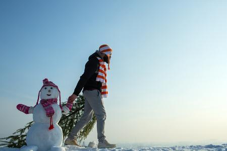 Mens en sneeuwman die op blauwe hemel lopen. Hipster slepende Kerstmis boom op besneeuwde winter weg. Kerel en sneeuwbeeld die hoeden en sjaals dragen. Kerstmis en Nieuwjaar. Vakantie feest concept, kopie ruimte Stockfoto - 86865164