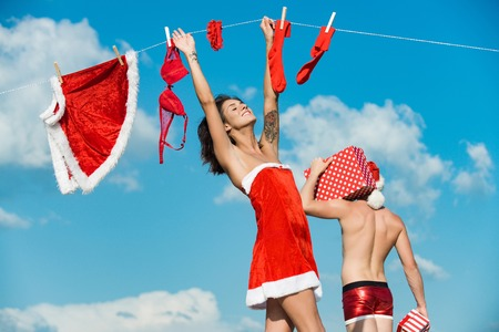 New year guy with muscular body on blue sky. Christmas man and woman family. Couple in love of man and girl hanging clothes for drying. Laundry and dry cleaning. Xmas red costume on rope with pin. Stock Photo