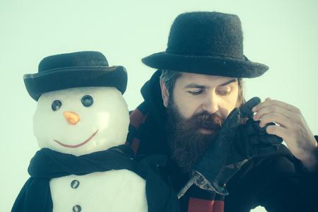 Heren in zwarte hoeden en sjaals op blauwe hemel. Mens die met baard handschoenen op stok zet. Sneeuwman met smileygezicht. Kerstmis en Nieuwjaar concept. Wintervakanties