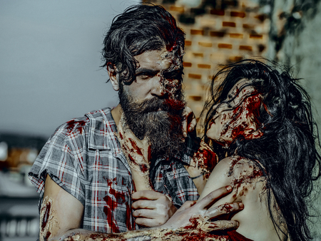 Halloween vampire with beard and red blood wounds outdoors. Horror and violence. Girl with bloody brunette hair. Holiday celebration concept. Woman strangling man with bloody hands. Stock Photo