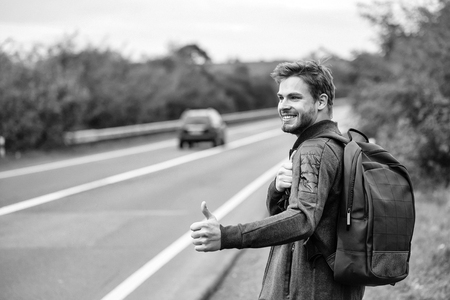 Young guy with beard on sexy smiling handsome face in casual clothes black backpack standing near road way hitchhiking autostop with hand outdoor Stock Photo