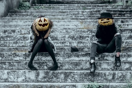 Halloween girls with pumpkin heads. Women sitting on grey stairs. Jack o lantern with smiley faces. Halloween holiday celebration concept.