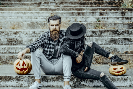 Halloween couple sitting on grey stairs. Bearded hipster smoking cigarette. Man and woman with pumpkins. Bad habits and unhealthy lifestyle concept. Halloween holiday celebration. Stock Photo