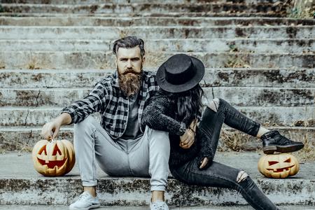 Halloween-paarzitting op grijze treden. Bebaarde hipster rokende sigaret. Man en vrouw met pompoenen. Slechte gewoonten en een ongezond levensstijlconcept. Halloween-vakantie vieren.