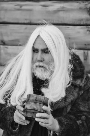Druid old man with long grey hair and beard on serious face with wooden mug in hands outdoor on wood background Stock Photo