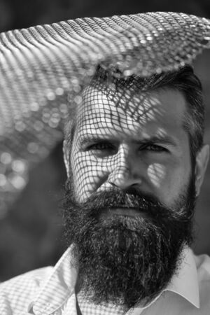 handsome young man with long beard and moustache on serious face with metallic net sunny day outdoor Banco de Imagens